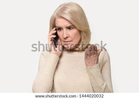 Headshot of annoyed old woman having argument talking via smartphone. Angry aged female speak irritated by cell phone, find out bad news over telephone. Portrait of lady with mobile isolated on grey