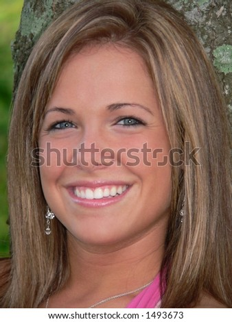 Headshot of attractive caucasian teenage girl with big, friendly smile. She has blond hair and blue eyes and is tanned.