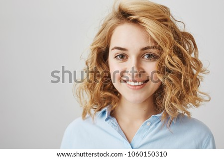 Headshot of attractive female coworker in blue blouse with short blonde curly hair, smiling with confident and friendly expression, being ready to help customer, posing over gray background #1060150310