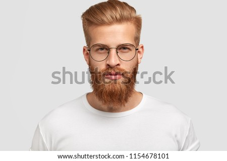 Headshot of attractive serious Caucasian male with thick ginger beard and trendy haircut, dressed in casual white t shirt, looks directly at camera, wears round glasses, isolated over white background