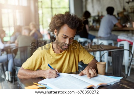 Headshot of attractive stylish dark-skinned student studying at coffee shop during lunch break, looking for information in book that he borrowed in library and writing down notes in his copybook