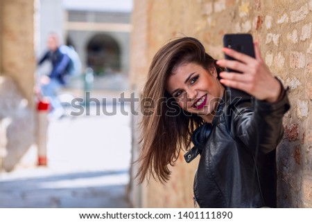 Headshot of brunette girl  taking selfie in the street.  #1401111890