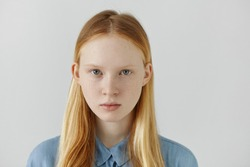 Headshot of Caucasian girl with freckles, blond hair and light eyes dressed in blue school shirt standing against white wall with empty space for advertisement. Youth and beauty. Human appearance