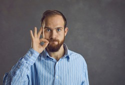 Headshot of confident handsome young caucasian guy showing secret silent gesture asking stop talking keep silence asking be quiet. People emotion and expression face portrait and confidentiality