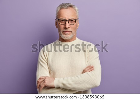 Headshot of confident mature European male pensioner keeps arms folded, wears optical glasses and white sweater, being sure in something, isolated over purple background. People and aging concept