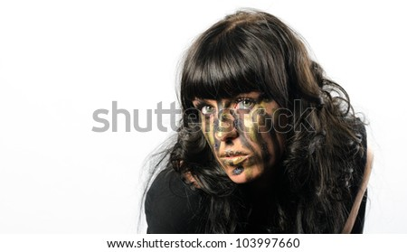 Headshot of darkhaired girl with facepaint streaks against a white background
