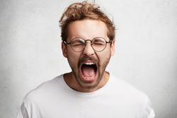 Headshot of emotional crazy male yells loudly, being irritated with someone or something, expresses negative emotions, isolated over white background. Mad stylish man shouts or screams at friend
