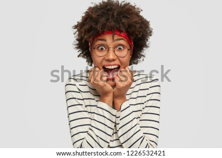 Headshot of emotive stunned black young woman opens mouth with amazement, keeps hands near mouth, wears casual striped sweater, optical glasses, models against white background. Emotions concept #1226532421
