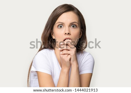 Headshot of frightened woman looking at fear eyes wide open. Studio portrait of terrified, stressed, scared to death young female biting her finger isolated on gray background. People emotions concept