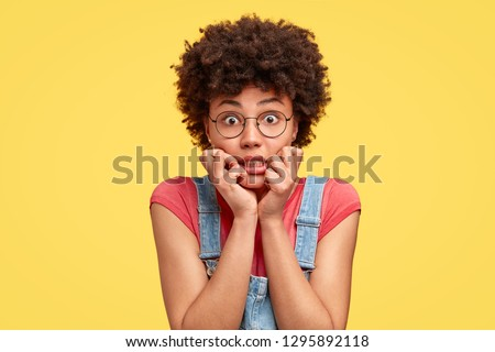 Headshot of frustrated mixed race young woman has crisp hair, bites finger nails with nervous expression, stares with eyes full of fear, wears casual clothes, stands against yellow studio wall #1295892118