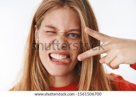 Headshot of funny emotive and charismatic young carefree girl making faces sticking out tongue showing peace gesture and winking expressing positive and excited emotions posing over grey background #1561506700