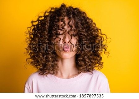 Headshot of girl with curly hairstyle wearing t-shirt send air kiss pouted lips isolated on vivid yellow color background