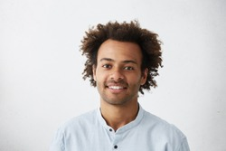 Headshot of good-looking positive young dark-skinned male with stubble and trendy haircut wearing blue shirt while posing isolated against blank studio wall background with copy space for your text