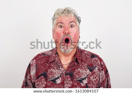 Headshot of goofy surprised bug-eyed  old senior man wearing casual shirt staring at camera with shocked look, expressing astonishment and shock, screaming Omg or Wow