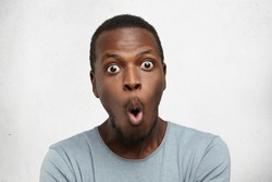 Headshot of goofy surprised bug-eyed young dark-skinned man student wearing casual grey t-shirt staring at camera with shocked look, expressing astonishment and shock, screaming