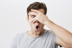 Headshot of goofy surprised bug-eyed young european male student wearing casual grey t-shirt staring at camera with shocked look, expressing astonishment and shock, hiding face behind his palm.
