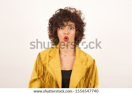 Headshot of goofy surprised bug-eyed young woman student wearing  yellow fringed jacket staring at camera with shocked look, expressing astonishment and shock, screaming Omg or Wow