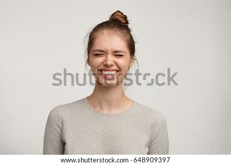 Headshot of gorgeous attractive young lady with hair gathered in bun smiling broadly and closing eyes, having impatient excited look, trying not to peep as her boyfriend preparing a surprise on her #648909397