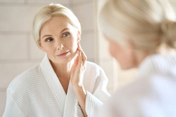 Headshot of gorgeous mid age adult 50 years old blonde woman standing in bathroom after shower touching face, looking at reflection in mirror doing morning beauty routine. Older skin care concept.