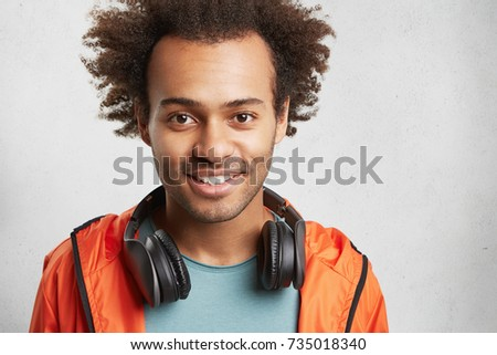 Headshot of handsome mixed race male with bushy hair, has good mood after listening loud rock music, smiles happily, demonstrates white perfect teeth. People, leisure and entertainment concept