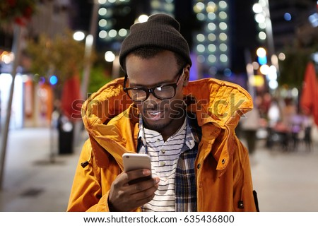 Headshot of handsome young Afro American student having walk around night city, holding mobile phone, using urban wifi, browsing pictures on social media. Modern technology and communication Foto stock ©