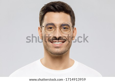 Headshot of handsome young man wearing white t-shirt and round glasses, looking straight to the camera with smile, isolated on gray background Foto d'archivio ©