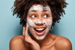 Headshot of happy black woman with foam or foaming cleanser on face, has facial treatments, gazes aside, opens mouth, has Afro hairstyle, isolated over light blue wall. Perfect clean skin concept