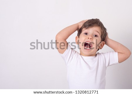 Headshot of impressed attractive little boy opening mouth from amazement and shock holding hands near face standing over white wall.