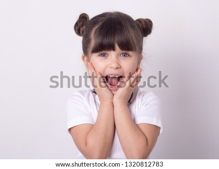 Headshot of impressed attractive little girl opening mouth from amazement and shock holding hands near face standing over white wall.
