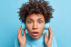 Headshot of impressed stunned curly haired woman has eyes popped out keeps breath listens music in wireless headphones shocked to hear very loud sound unexpectedly isolated on blue studio wall
