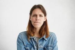 Headshot of indecisive confused young European woman in denim wear pursuing lips, her look expressing doubt and uncertainty as she has to come up with best solution while dealing with problem