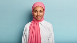 Headshot of lovely satisfied religious Muslim woman with gentle smile, dark healthy skin, wears pink scarf on head, white shirt, isolated over blue background, has no make up, natural beauty