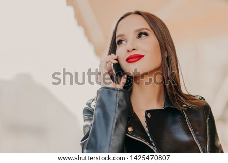 Headshot of pleasant looking dreamy woman focused aside, has telephone conversation, wears leather coat, notices someone into distance, poses over blurred background. Good roaming connection