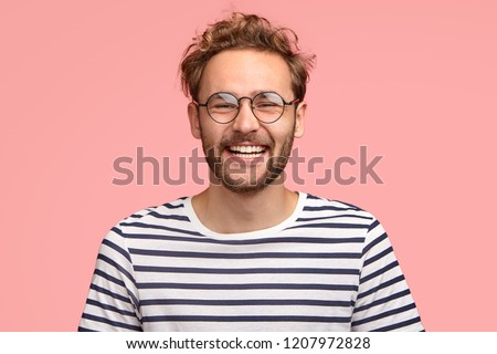 Headshot of pleased hipster has satisfied expression, curly hair and bristle, wears round transparent glasses and striped t shirt, feels glad after promotion at work, isolated over pink background