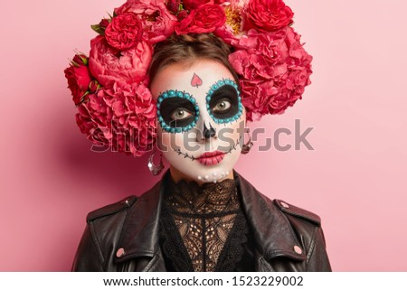 Headshot of serious beautiful woman wears sugar skull makeup, celebrates Mexican Day of dead, wears big earrings, flower wreath, black leather jacket. People, death, Halloween, celebration concept #1523229002