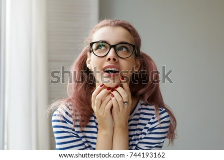 Headshot of smart cunning young woman in black rimmed glasses and striped top touching her face and looking up with sly or mysterious expression, opening mouth while planning or scheming something #744193162