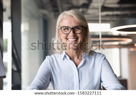 Headshot of smiling middle-aged businesswoman in glasses look at camera pose shooting live webinar broadcast in office, happy mature female employee talk on video call at workplace, leadership concept
