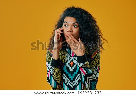 Headshot of stunned emotional dark skinned woman gasps from fear, hears unpleasant news, has phone conversation, wears colorful sweater, models over yellow background. Omg concept