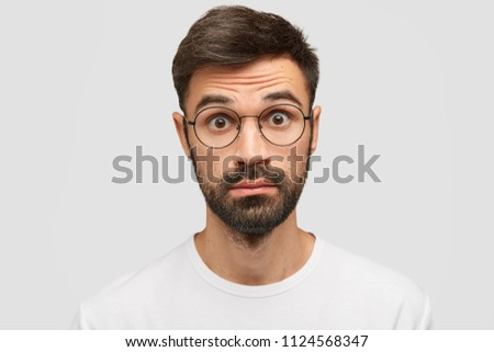 cf8dd877a1 Free photos Young man with a surprised expression and thick glasses ...