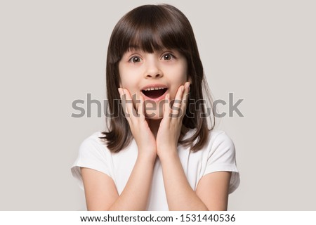 Headshot of surprised little preschooler girl look at camera feel stunned amazed by unexpected good news, happy small child isolated on grey studio background shocked by unbelievable surprise