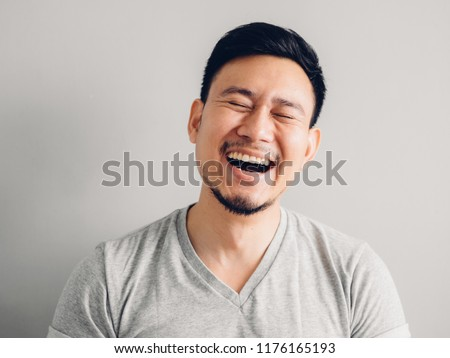 Headshot photo of Asian man with laugh face. on grey background.