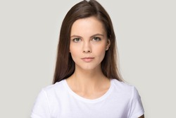 Headshot picture of beautiful young woman model in white t-shirt isolated on grey studio background posing, portrait of pretty millennial female brunette look at camera shooting casting