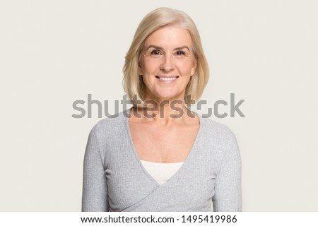 Headshot picture of happy Caucasian senior woman stand isolated on grey studio background look at camera, portrait of smiling aged female with gray hair stand posing, elderly help assistance concept