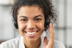 Headshot portrait close-up smiling African American woman support service operator in headset wireless headphones with microphone, smiling, working and looking at the camera, satisfied worker concept