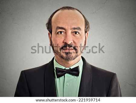 headshot portrait mature gentleman handsome man in elegant black suit wearing bow tie isolated on grey wall background. Positive face expression handsome man in elegant black suit