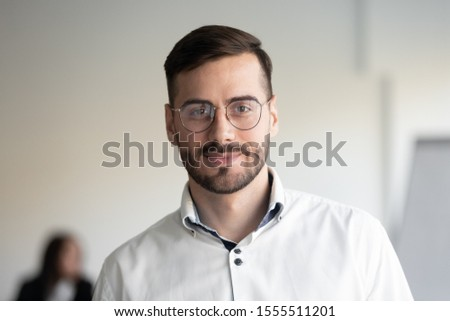 Headshot portrait of confident millennial businessman in glasses stand posing in modern office, smiling successful male ceo or boss wearing spectacles look at camera, leadership concept