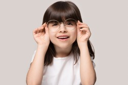 Headshot portrait of cute little preschooler girl isolated on grey studio background wear glasses look at camera, small child try spectacles at opticians, kid eyesight correction treatment concept