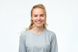Headshot portrait of happy blonde girl in blue pulover smiling looking at camera. White background. Positive facial human emotion.