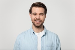 Headshot portrait of happy millennial man in casual clothes isolated on grey studio background posing, smiling young male in shirt look at camera with wide healthy teeth, demonstrated dental treatment