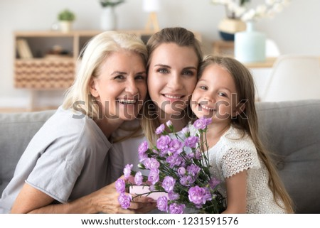 Headshot portrait of happy three generations women family celebrating mothers day birthday together, smiling grandmother and kid daughter congratulating young mom with flowers gift looking at camera